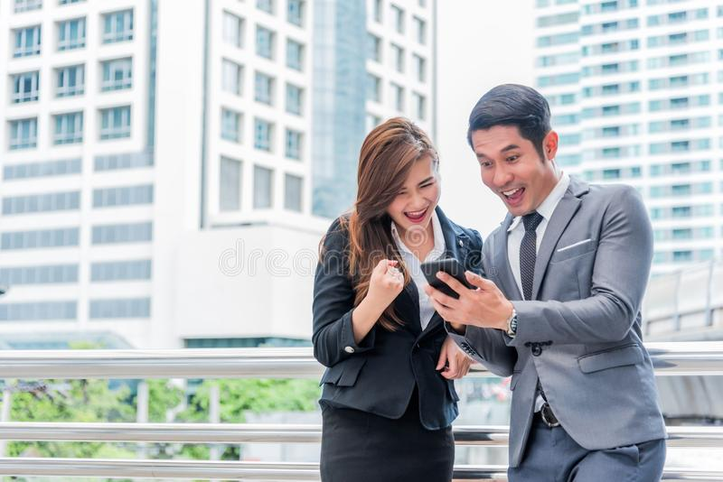 Biznesmen i jego sekretarka zaskakujemy gdy spojrzenie przy smartphone, Biznesowy pojęcie, szczęścia pojęcie, technologii pojęcie obrazy stock
