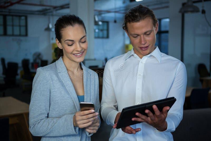Biznesmen i kolega dyskutuje nad cyfrową pastylką i telefonem komórkowym obrazy royalty free