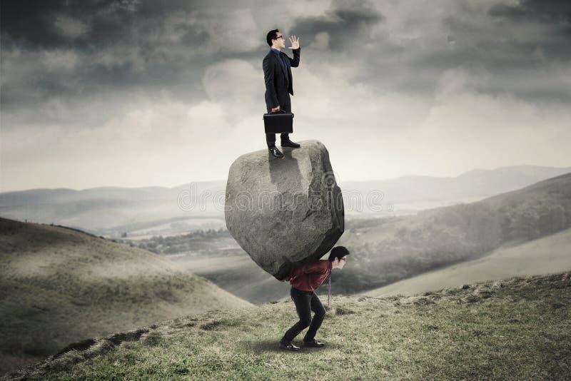 Biznesmen i partner z ciężarem w wzgórzu obrazy stock
