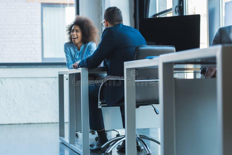biznesmen i roześmiany amerykanin afrykańskiego pochodzenia bizneswomanu obsiadanie przy stołem zdjęcia stock