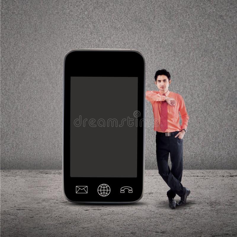 Biznesmen i smartphone na popielatym obrazy stock