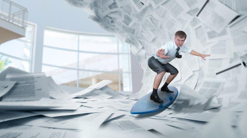 Biznesmen jedzie surfboard na stosach papiery fotografia stock