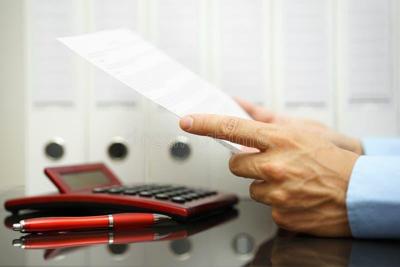 Biznesmen jest czytający pieniężnego dokument i sprawdzać z koszem zdjęcia stock