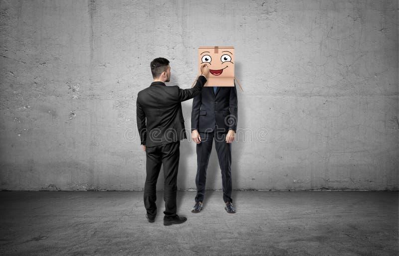Biznesmen jest rysunkowym szczęśliwym twarzą na pudełku który chuje inną mężczyzna ` s głowę zdjęcia stock