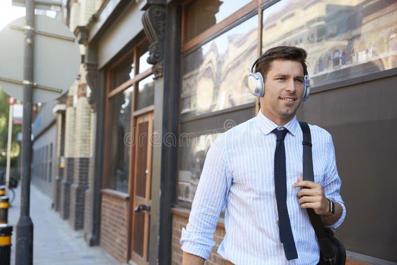 Biznesmen Jest ubranym Bezprzewodowych hełmofony Chodzi Pracować obrazy stock