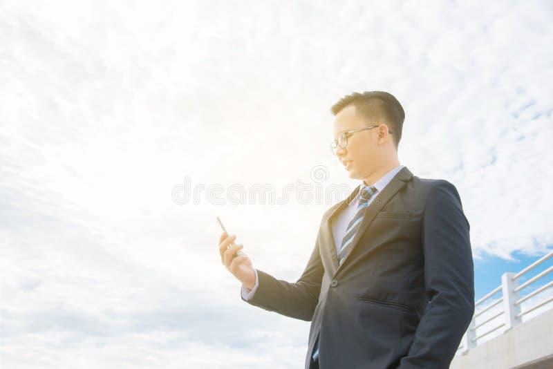 Biznesmen jest ubranym czarnego kostium ono uśmiecha się podczas gdy używać telefon komórkowego zdjęcie royalty free