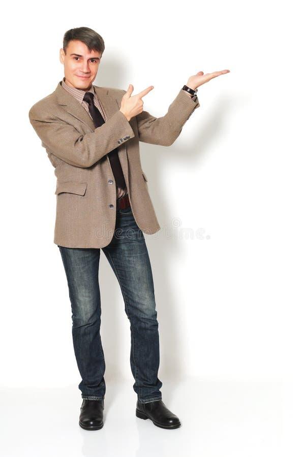 Biznesmen jest ubranym kurtki koszula, cajgi na lekkim tle i zdjęcia stock