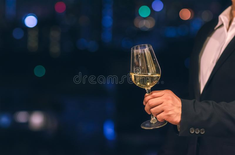 Biznesmen jest ubranym marynarki wojennej błękita koloru kostiumu stojaki przy dachu barem wznosi toast szkło biały wino z ciemny obrazy stock