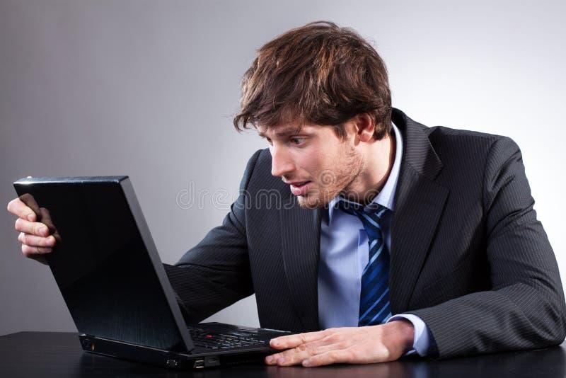 Biznesmen jest usytuowanym przy jego biurkiem i patrzeje komputer zdjęcie royalty free
