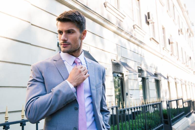 biznesmen krawat prostuje krawat zdjęcia stock