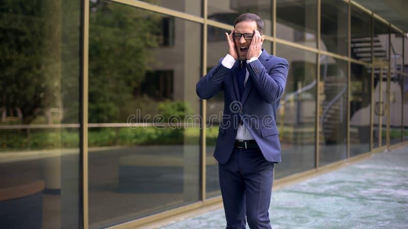 Biznesmen krzyczy od nagłego ostrego migrena ataka, ryzyko skrzeplina, zdrowie zdjęcie stock