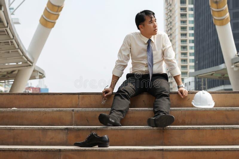 Biznesmen który jest zmęczony lub zaakcentowany siedzący na schodkach samotnie zdjęcie royalty free