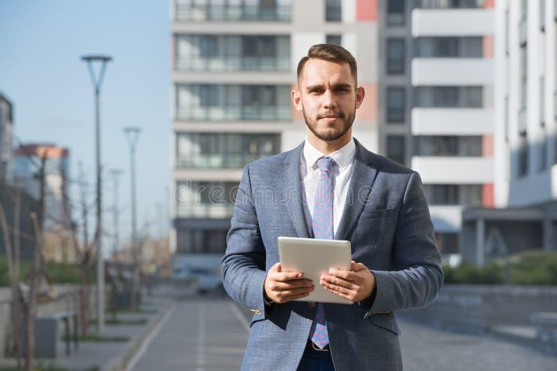 Biznesmen lub agent nieruchomości z pastylka komputerem przeciw nowemu budynkowi zdjęcia stock