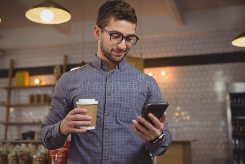 Biznesmen ma kawę podczas gdy używać telefon w kawiarni zdjęcia royalty free