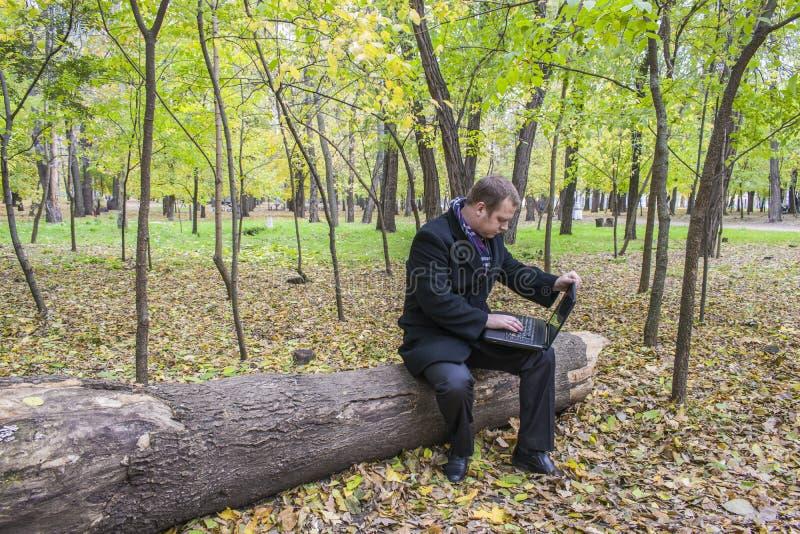 Biznesmen ma laptop w parku w spadku Mężczyzna pracuje przy komputerem w parku obrazy royalty free