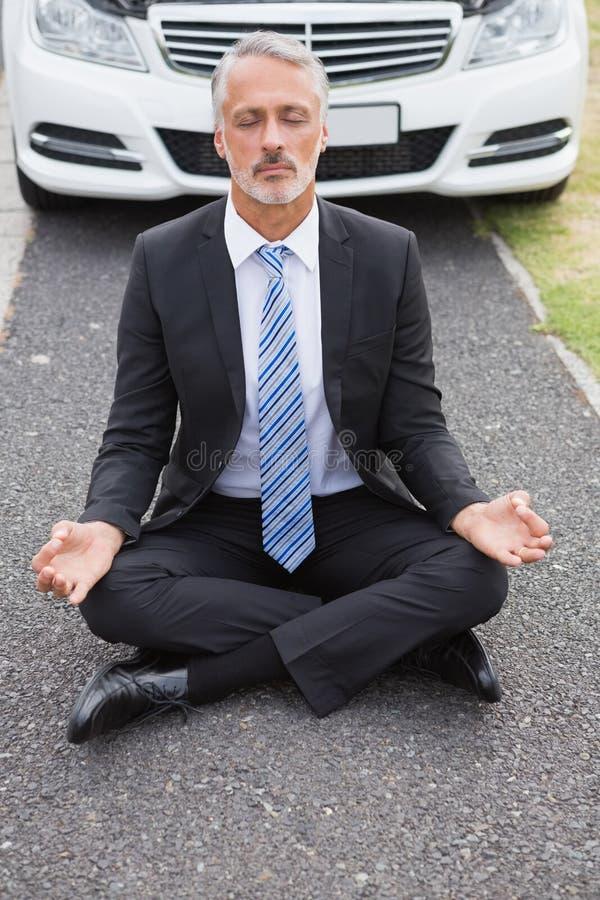 Biznesmen medytuje po jego samochód łamającego puszka obrazy royalty free
