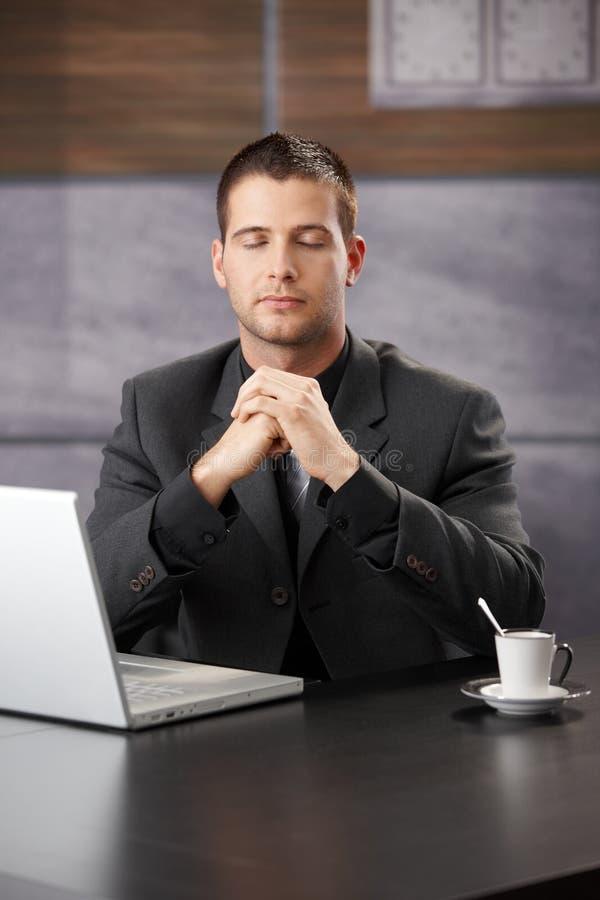 Biznesmen medytuje przy biurkiem obrazy royalty free