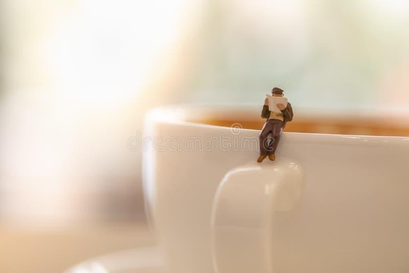 Biznesmen miniatury postaci czytanie i obsiadanie gazeta na białej filiżance gorąca kawa z odbitkowym głąbikiem obrazy stock