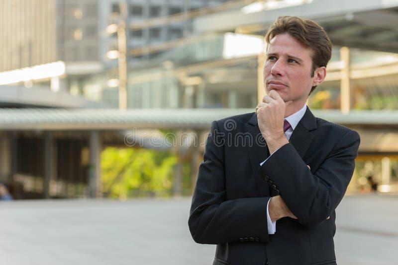 Biznesmen myśleć outdoors przed nowożytnym budynkiem obraz royalty free