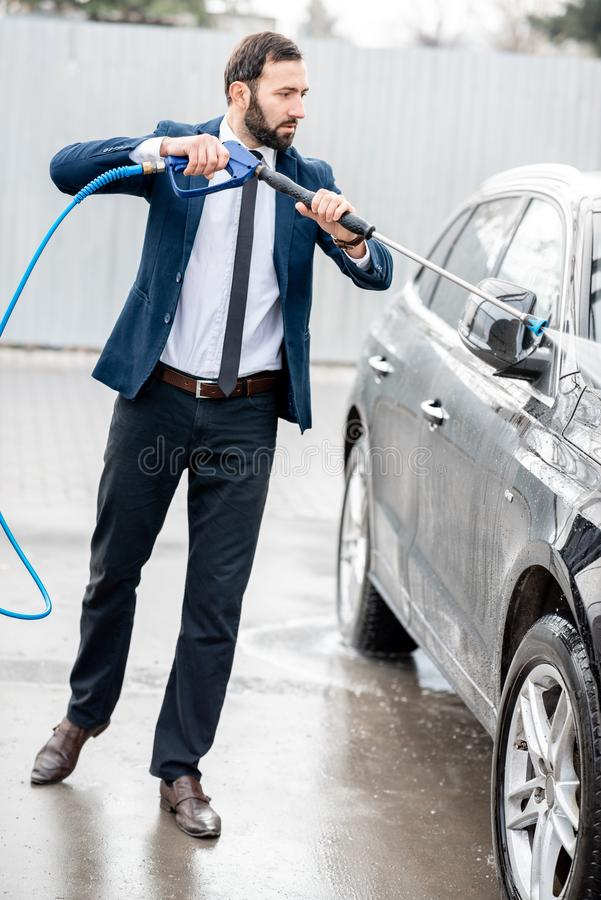 Biznesmen myje jego samochód zdjęcia royalty free