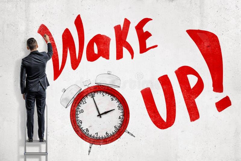 Biznesmen na drabinowym obszyciu ściana z czerwień znakiem «budzi się «i czerwony budzik odizolowywający na białym tle zdjęcia royalty free