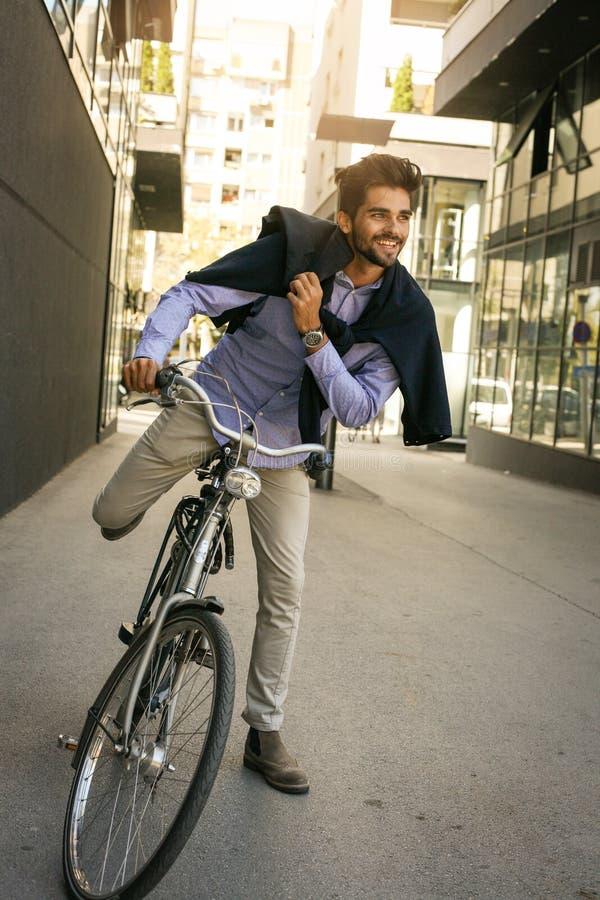 Biznesmen na rowerze Biznesowy mężczyzna opuszcza jego pracę obraz royalty free
