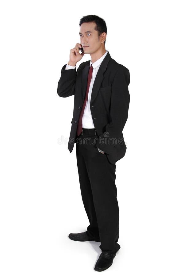 Biznesmen na telefonie, pozyci i przyglądającym up, obraz stock