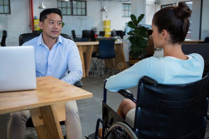 Biznesmen oddziała wzajemnie z niepełnosprawnym kolegą obrazy stock