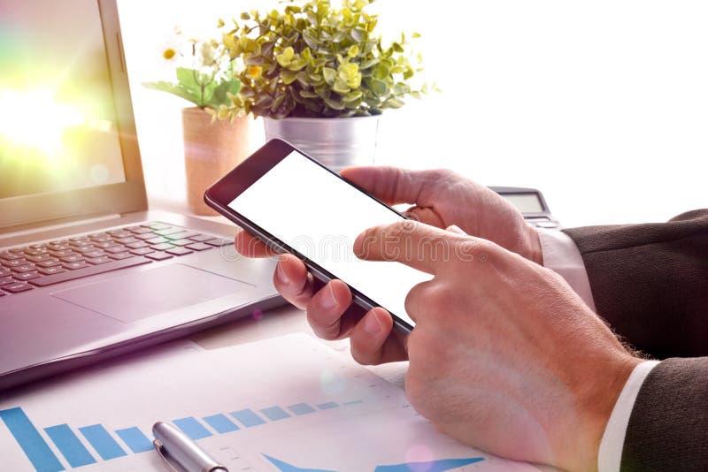 Biznesmen oddziała wzajemnie z telefonem komórkowym w biurze obrazy royalty free