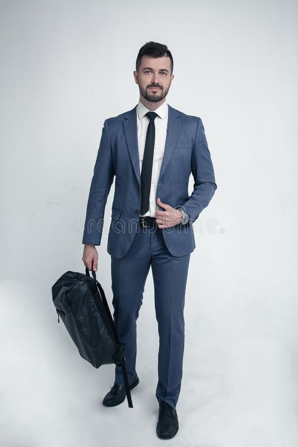 Biznesmen odizolowywający na białym tle ubierał w kostiumu chodzi kamera z torbą w jego rękach zdjęcie stock