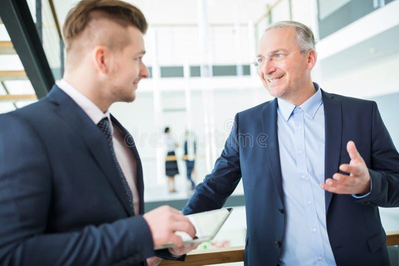 Biznesmen ono Uśmiecha się Podczas gdy Opowiadający kolega obraz stock