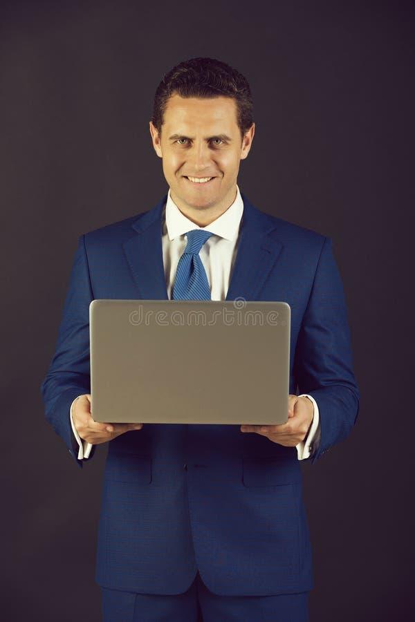 Biznesmen ono u?miecha si? z laptopem obraz royalty free