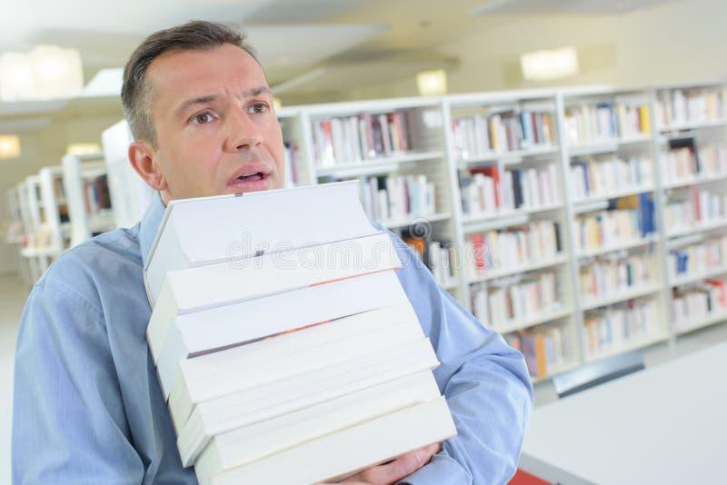 Biznesmen ono zmaga się trzymający wiele książki życzy promującym zdjęcia stock