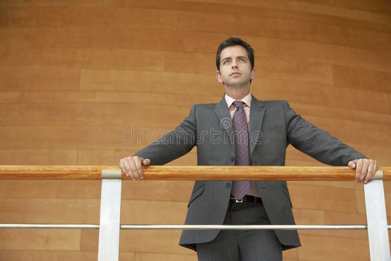 Biznesmen Opiera Na poręcz pozyci Przeciw Drewnianej ścianie zdjęcie stock