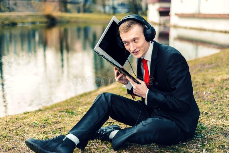 Biznesmen opowiada na laptopie w hełmofonach Internetowa komunikacja młody facet w kostiumu na naturze freelancer, odległy obraz stock