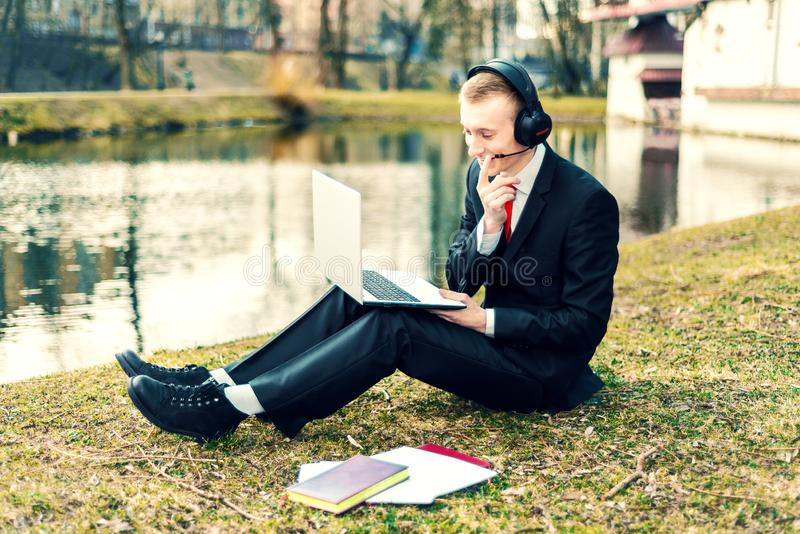 Biznesmen opowiada na laptopie w hełmofonach Internetowa komunikacja młody facet w kostiumu na naturze freelancer, odległy zdjęcie royalty free