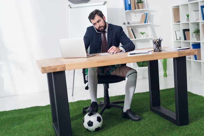 biznesmen opowiada na smartphone przy miejscem pracy z piłki nożnej piłką obraz stock