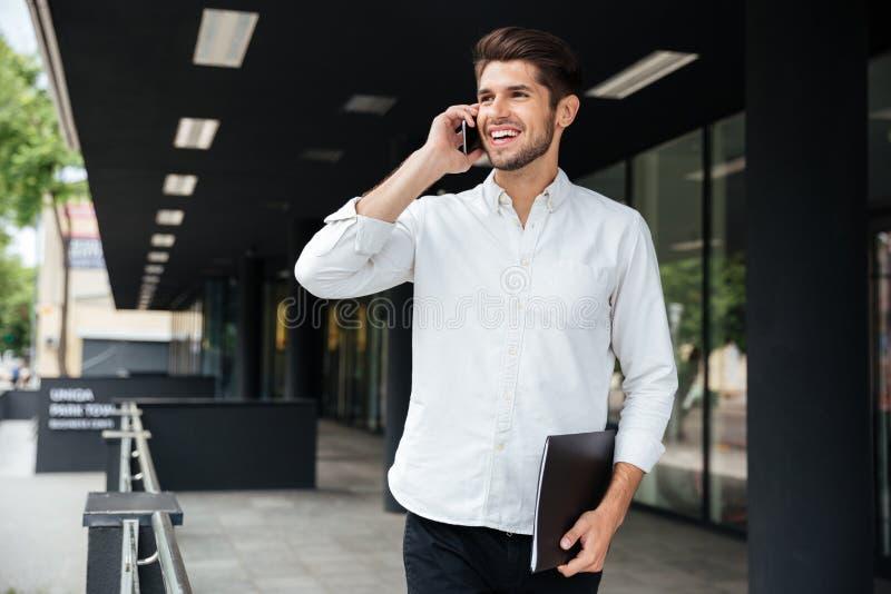 Biznesmen opowiada na telefonie komórkowym blisko centrum biznesu z falcówką obrazy royalty free