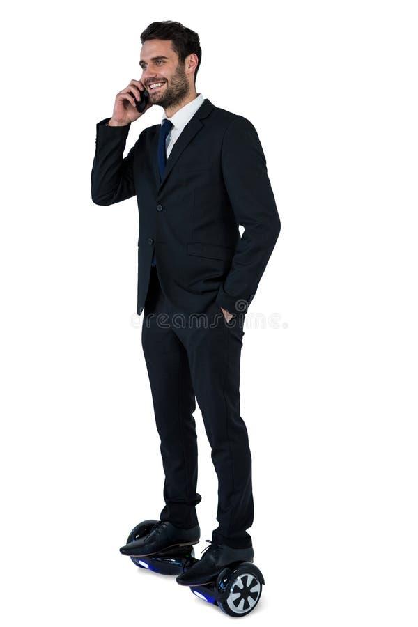 Biznesmen opowiada na telefonie komórkowym na hoverboard fotografia stock
