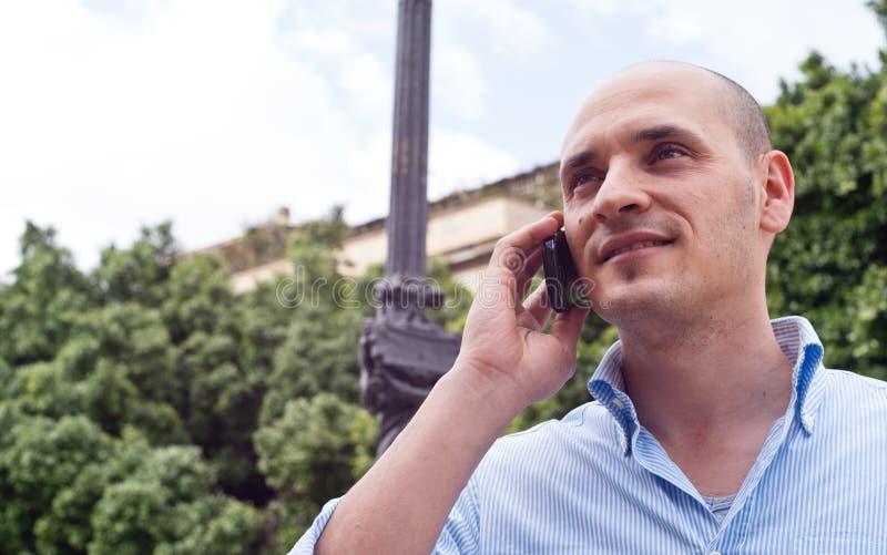 Biznesmen opowiada na telefonie komórkowym outdoors obrazy royalty free