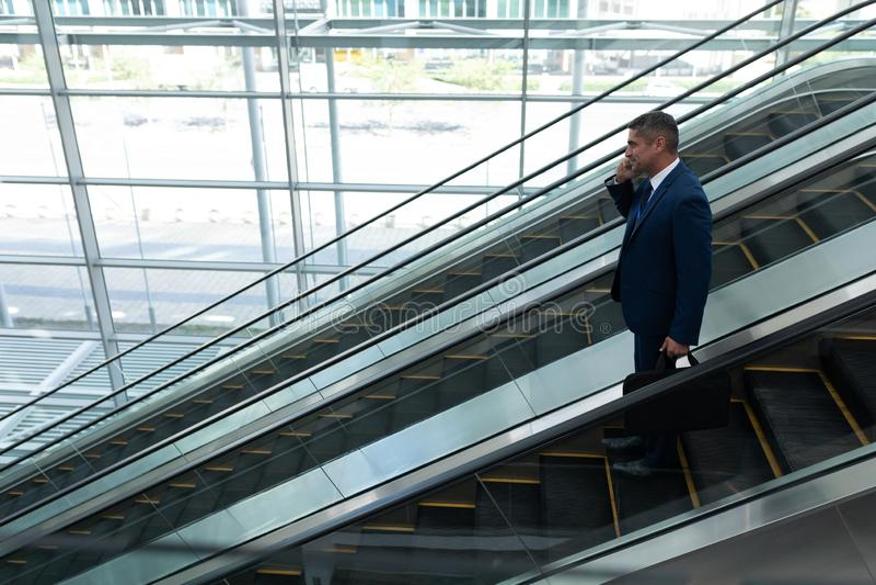 Biznesmen opowiada na telefonie komórkowym podczas gdy ruszający się w dół na eskalatorze obraz royalty free