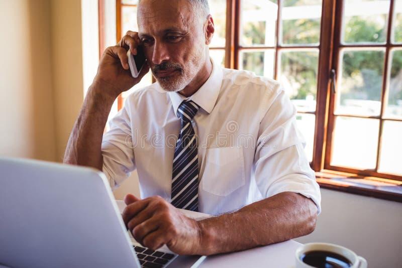 Biznesmen opowiada na telefonie komórkowym podczas gdy używać laptop obrazy stock