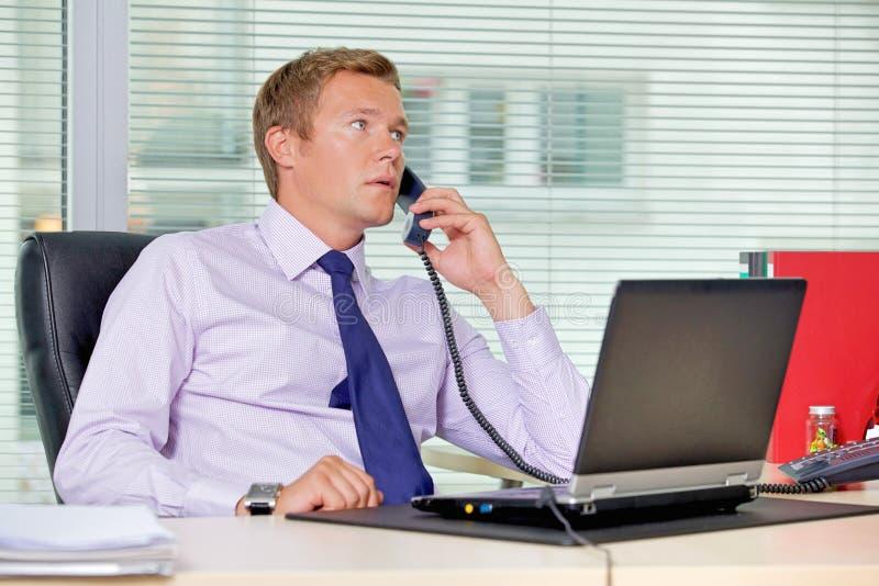 Biznesmen opowiada na telefonie przy biurem z laptopem na stole zdjęcia royalty free