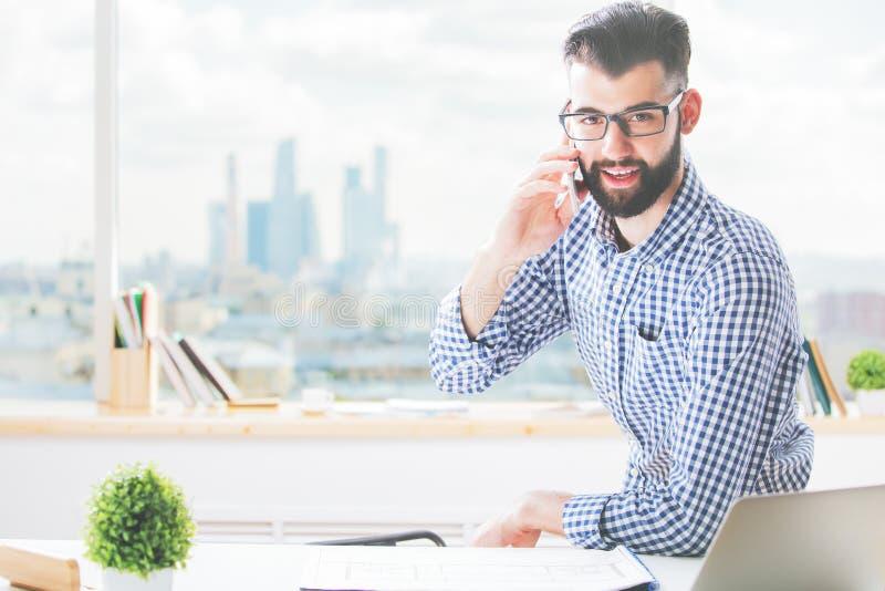 Biznesmen opowiada na telefonie przy pracą fotografia stock