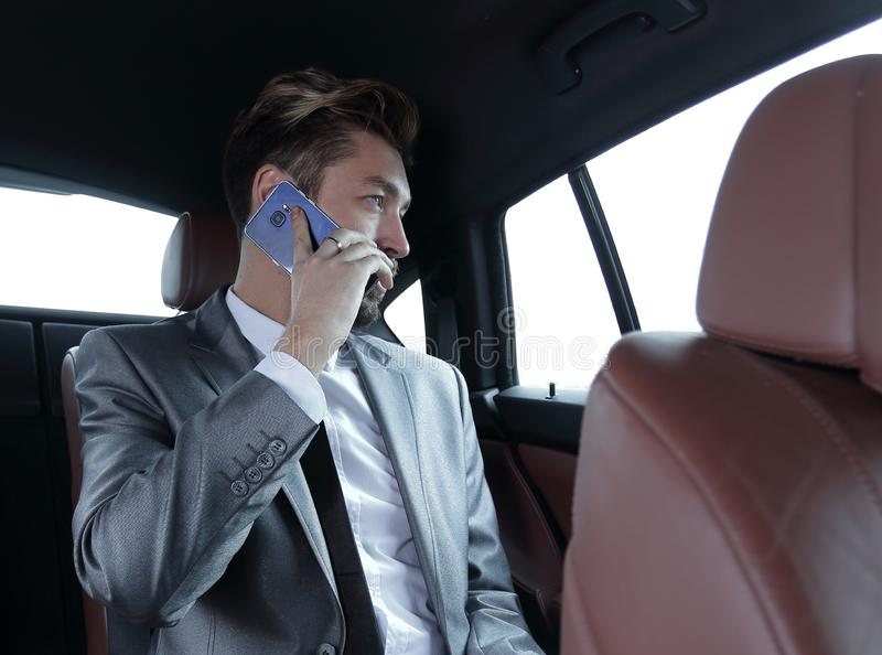 Biznesmen opowiada na telefonie w plecy zdjęcia stock