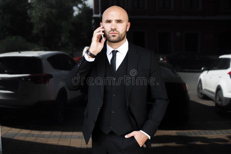 Biznesmen opowiada na telefonie z torbą blisko biura zdjęcie royalty free