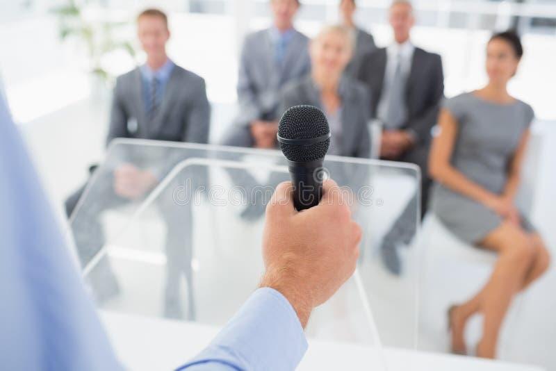 Biznesmen opowiada w mikrofonie podczas konferenci obraz royalty free