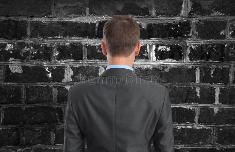 Biznesmen patrzeje ściana z cegieł zdjęcia royalty free