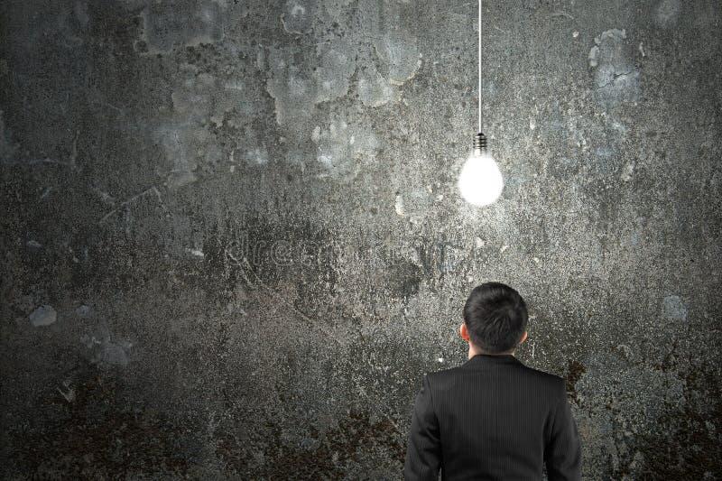 Biznesmen patrzeje żarówkę jaskrawy iluminował zmrok conc obraz stock