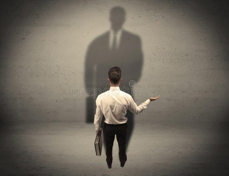 Biznesmen patrzeje dużego cienia pojęcie obrazy stock